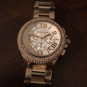 A gold Michael kors watch with diamond around it